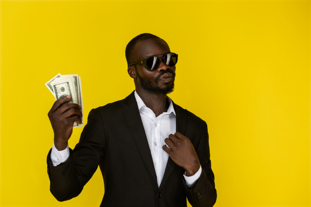 bearded-afroamerican-guy-is-holding-dollars-one-hand-wearing-sunglasses-black-suit_8353-10356